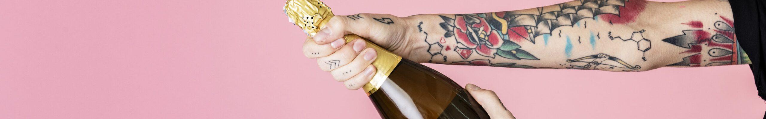 Tattooed feminine hand holding a bottle of champagne